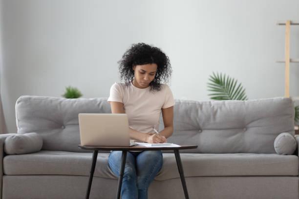 african woman sitting at coffee table holding pen writing - telecomando foto e immagini stock