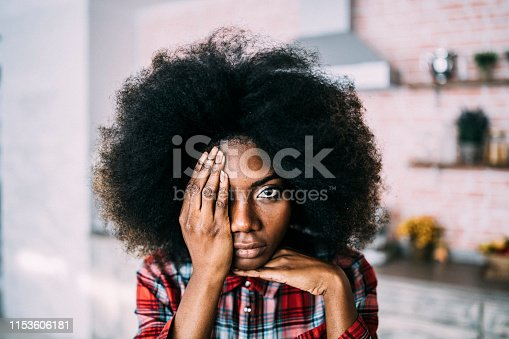 African woman hiding her face with hands.