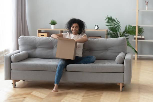 afrikanische frau sitzt auf couch auspacken empfangen paket fühlt sich glücklich - bekommen stock-fotos und bilder