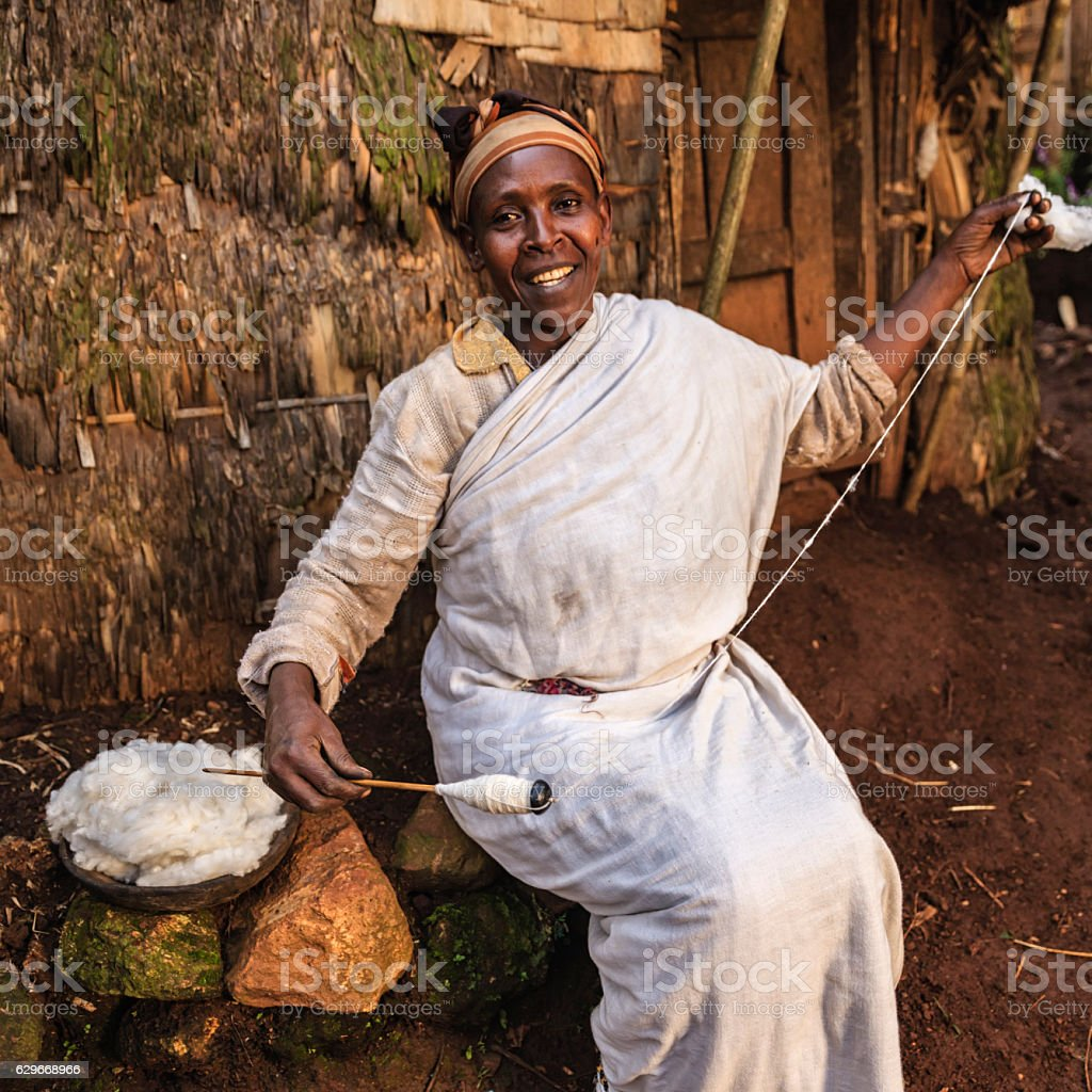 African woman spinning a wool, East Africa stock photo