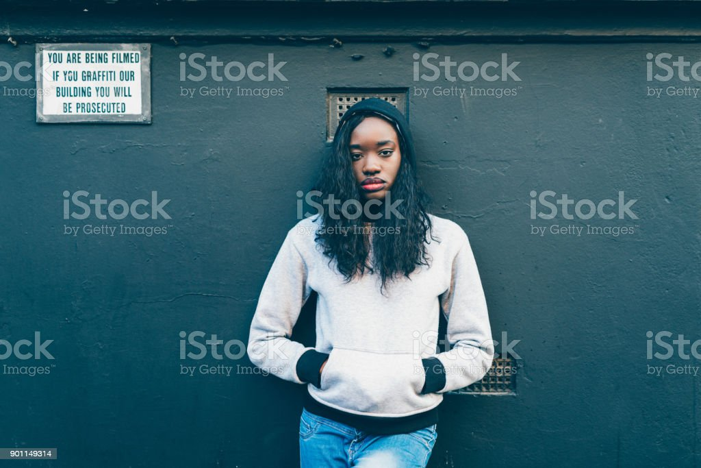 African woman standing near the wall with warning sign stock photo