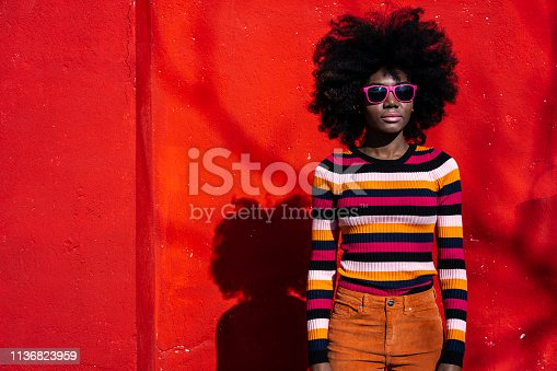 African woman standing in front of red colored wall.