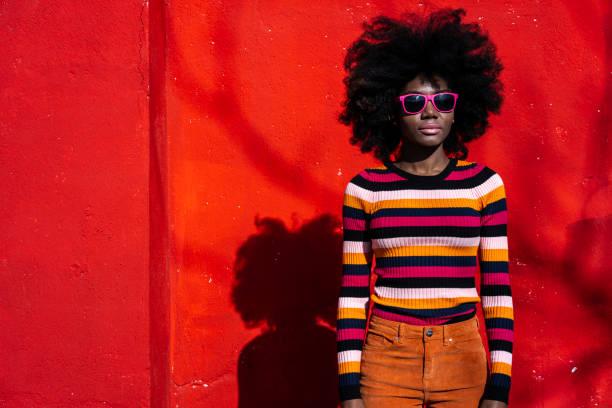 빨간색 배경에 서 있는 아프리카 여자 - 아프로 머리 뉴스 사진 이미지