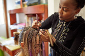 African woman making braids to her friend.