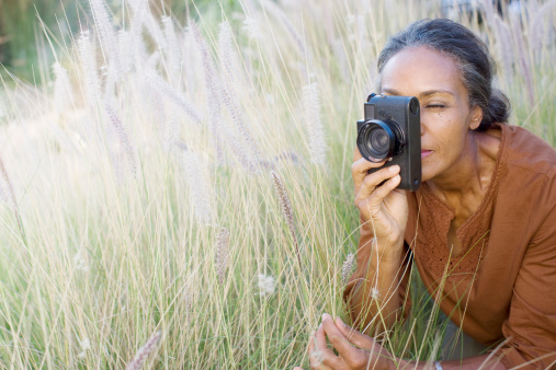African woman taking photographs outdoors