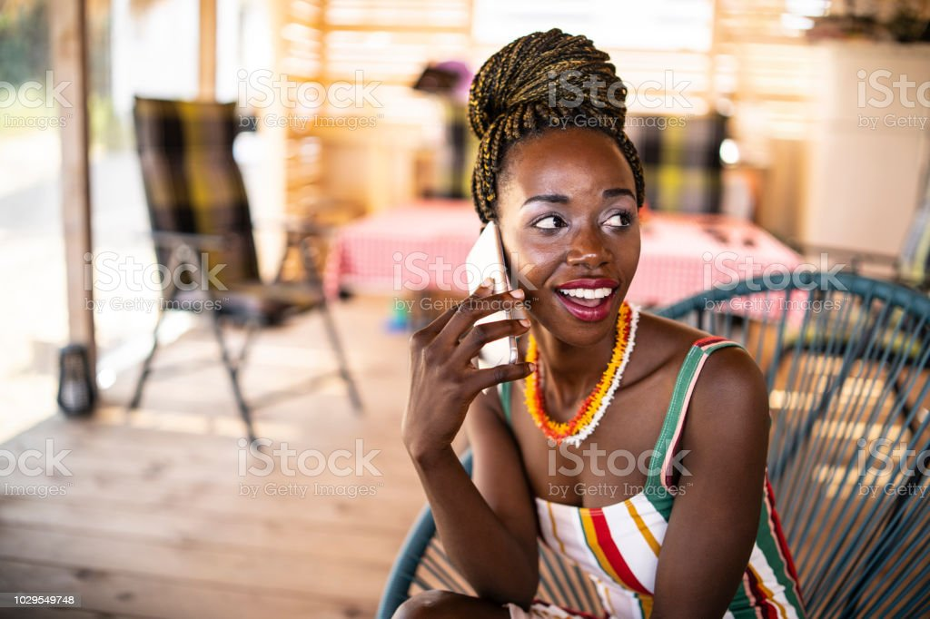 Carefree young african woman sitting on porch and talking on smart...
