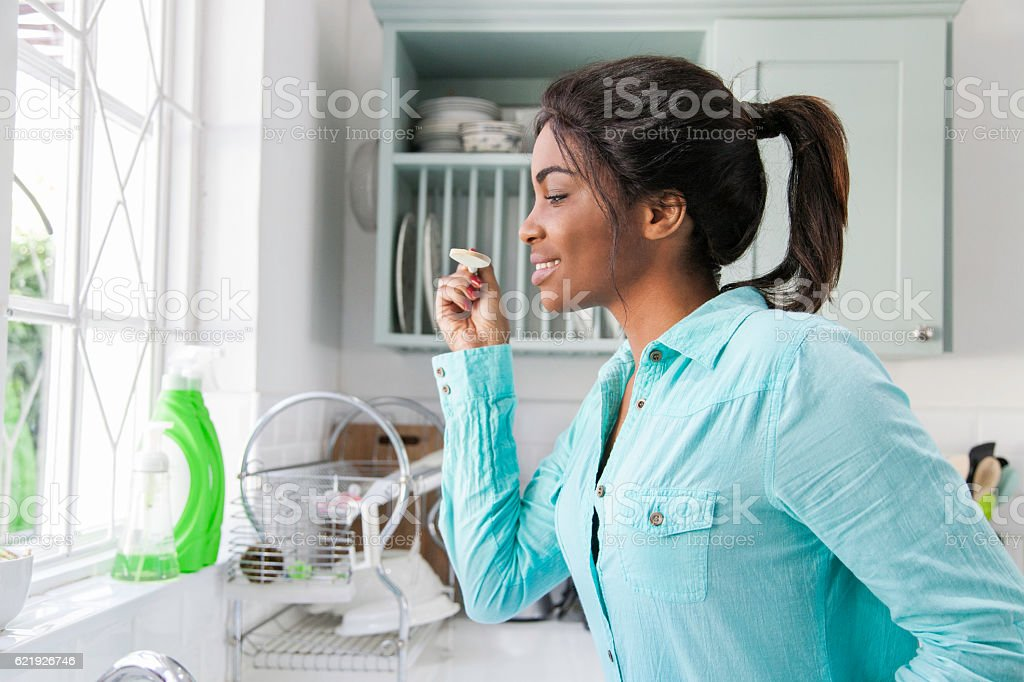 African woman tasting food. stock photo