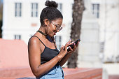 A young black African woman stands outside and types on her mobile phone