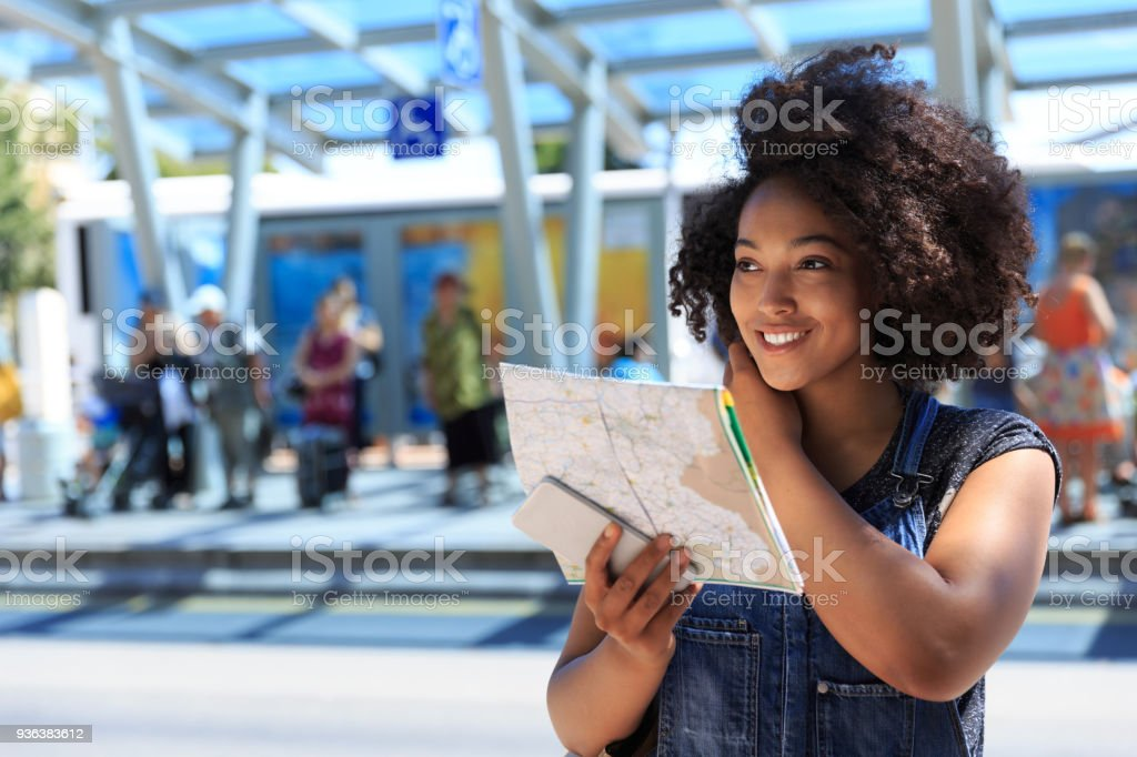 African woman using a map on bus station