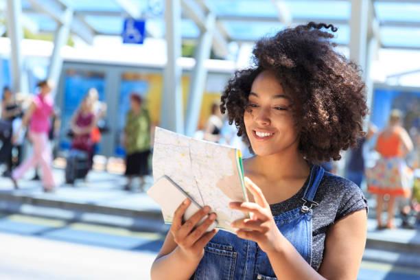 afrikanerin mit hilfe einer karte am busbahnhof - geführtes lesen stock-fotos und bilder