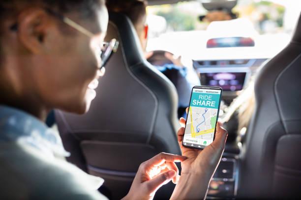 mujer africana usando la aplicación para compartir coches - uso compartido del coche fotografías e imágenes de stock