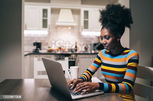 822557072 istock photo African Woman using laptop at home at night 1202687008