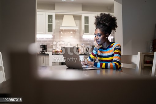 822557072 istock photo African Woman using laptop at home at night 1202687018