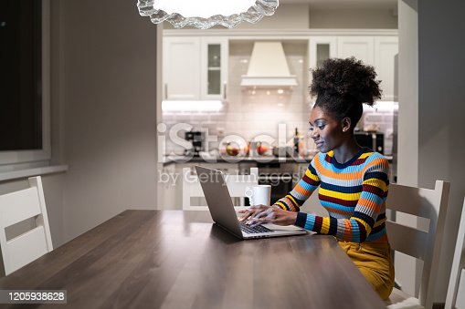 822557072 istock photo African Woman using laptop at home at night 1205938628