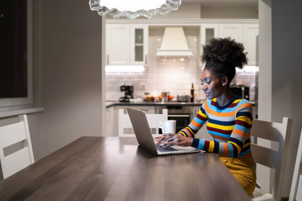 African Woman using laptop at home at night
