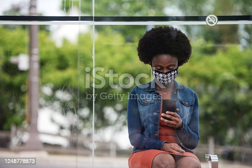 African woman waiting for bus, wearing and homemade mask, Quebec, Canada