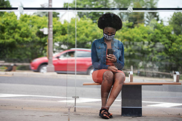 African woman waiting for bus stock photo