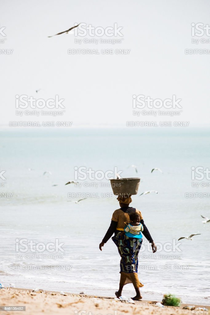 African woman walking at the beach - Gambia stock photo