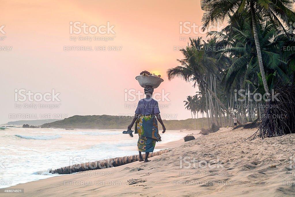 African woman walking on beautiful beach stock photo