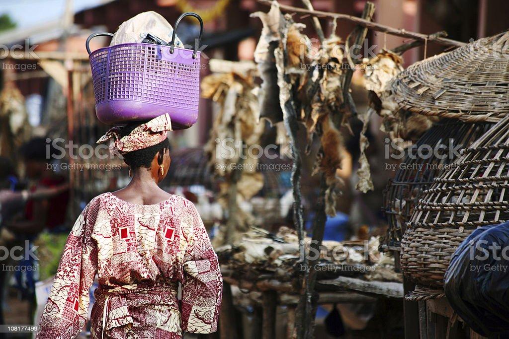 African Woman Walking Through Market stock photo
