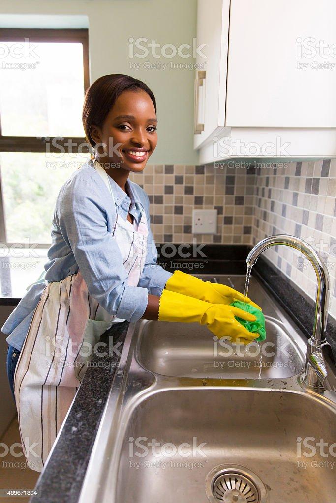 african woman washing dishcloth stock photo