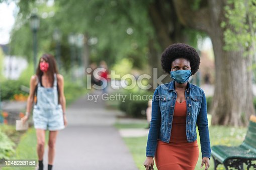 African woman in a park, relaxing, wearing and homemade mask, Quebec, Canada