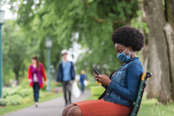 African woman wearing an homemade mask in a park stock photo