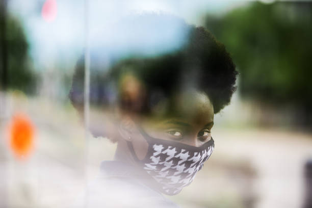 African woman wearing an homemade mask, waiting for bus stock photo