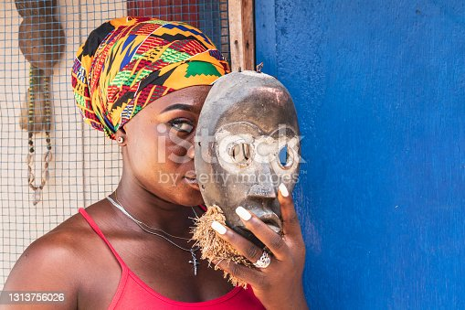 African woman with an old wooden mask in her hand