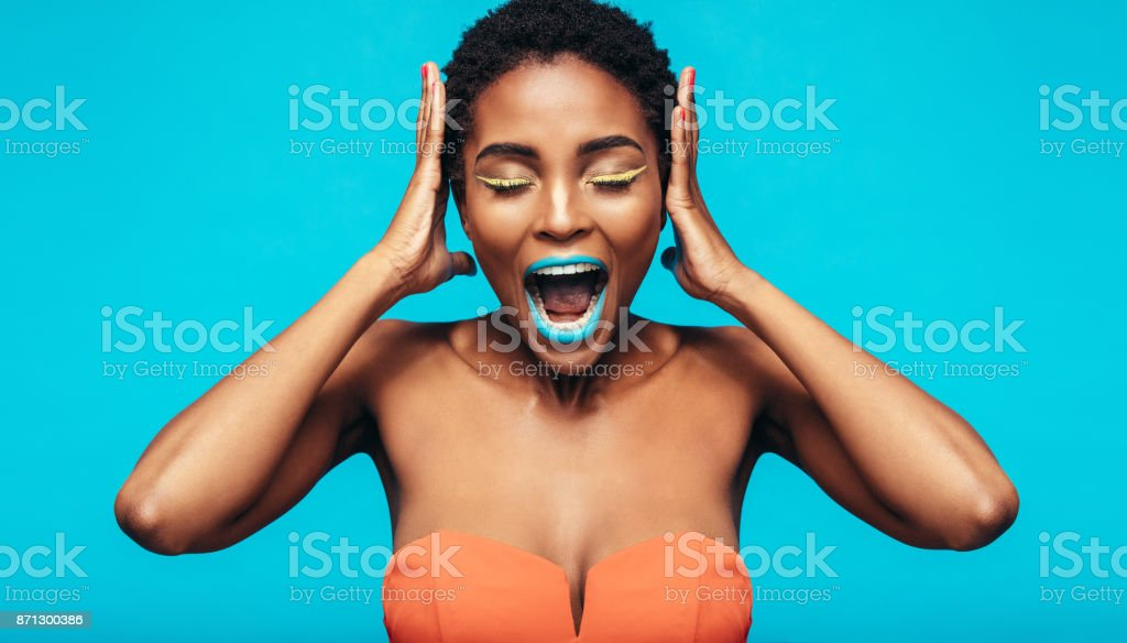 African woman with colorful makeup screaming stock photo