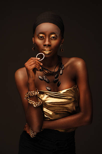 african woman with creative gold make–up and jewelry - damen top gold stock-fotos und bilder