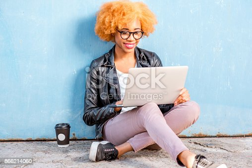 istock African woman with laptop on the blue background 866214060