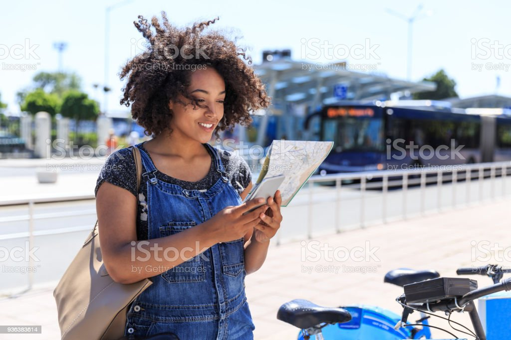 African tourist using a map and taking a bike on street.