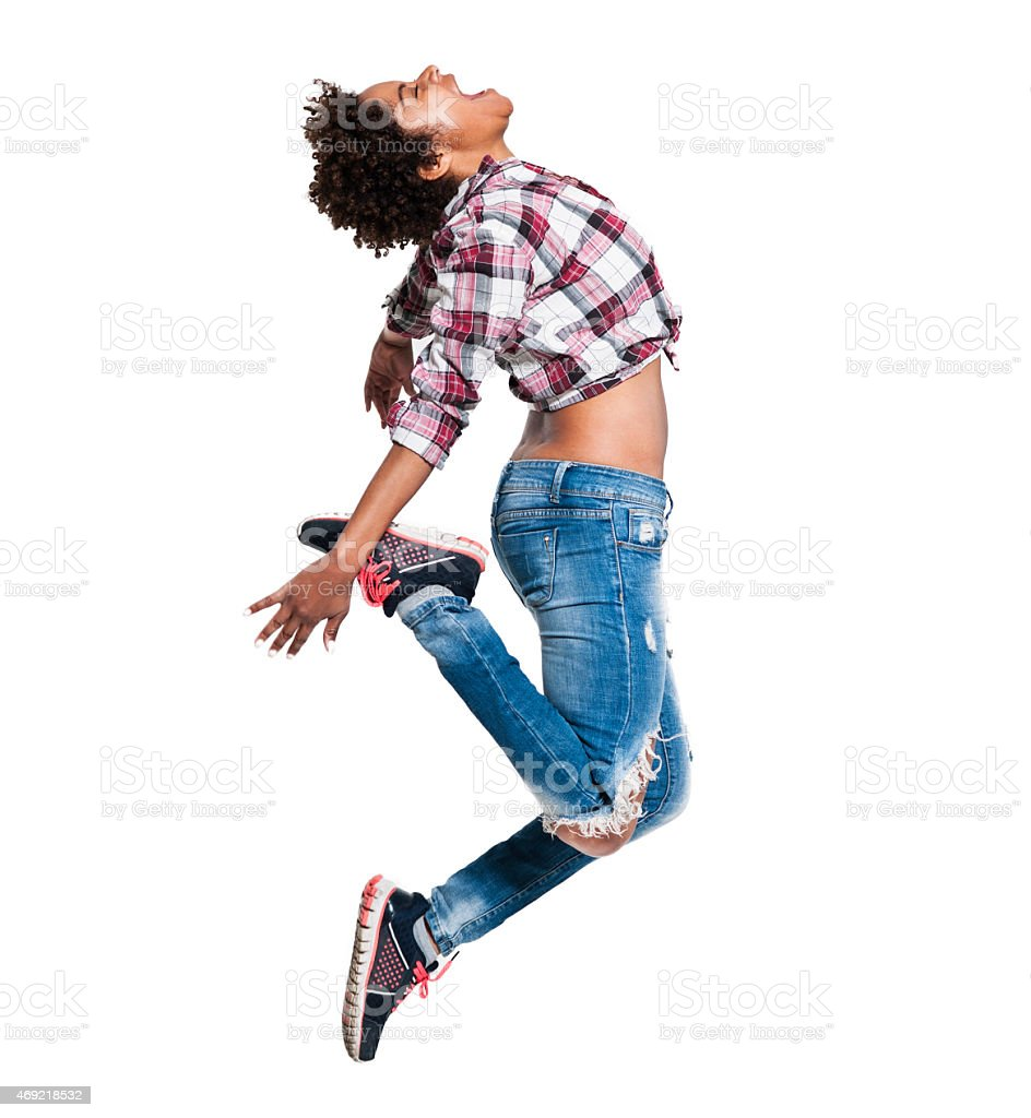 African woman with shirt tied above stomach in mid jump stock photo