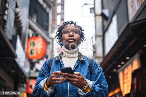 Young African female traveler attempting to find her way through the streets of urban Tokyo with a smartphone.