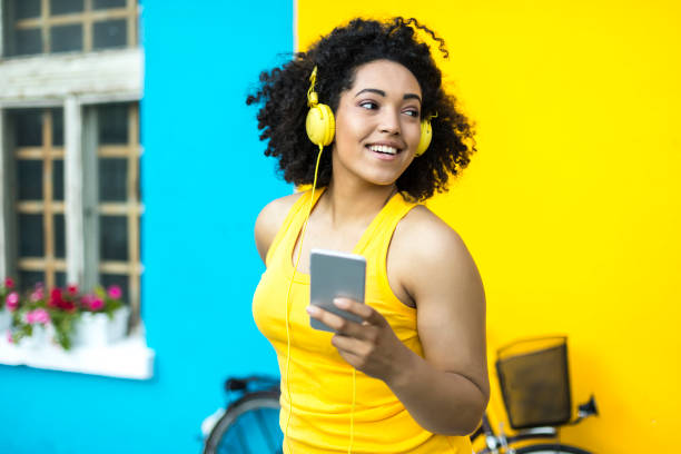 African woman  with yellow headphones using smart phone stock photo