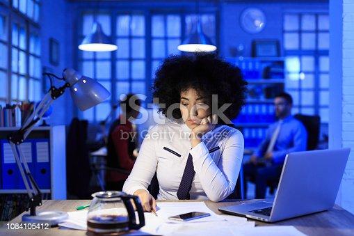 istock African woman working late 1084105412