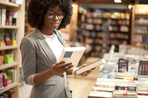 Women at bookstore choosing a book to buy