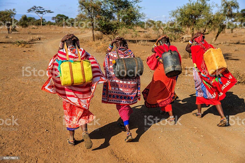 African women from Maasai tribe carrying water, Kenya, East Africa stock photo