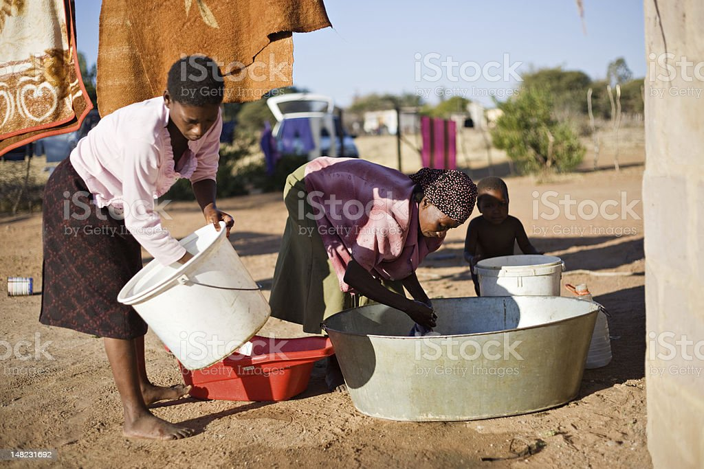 African women washing clothes outdoors in metal tubs stock photo
