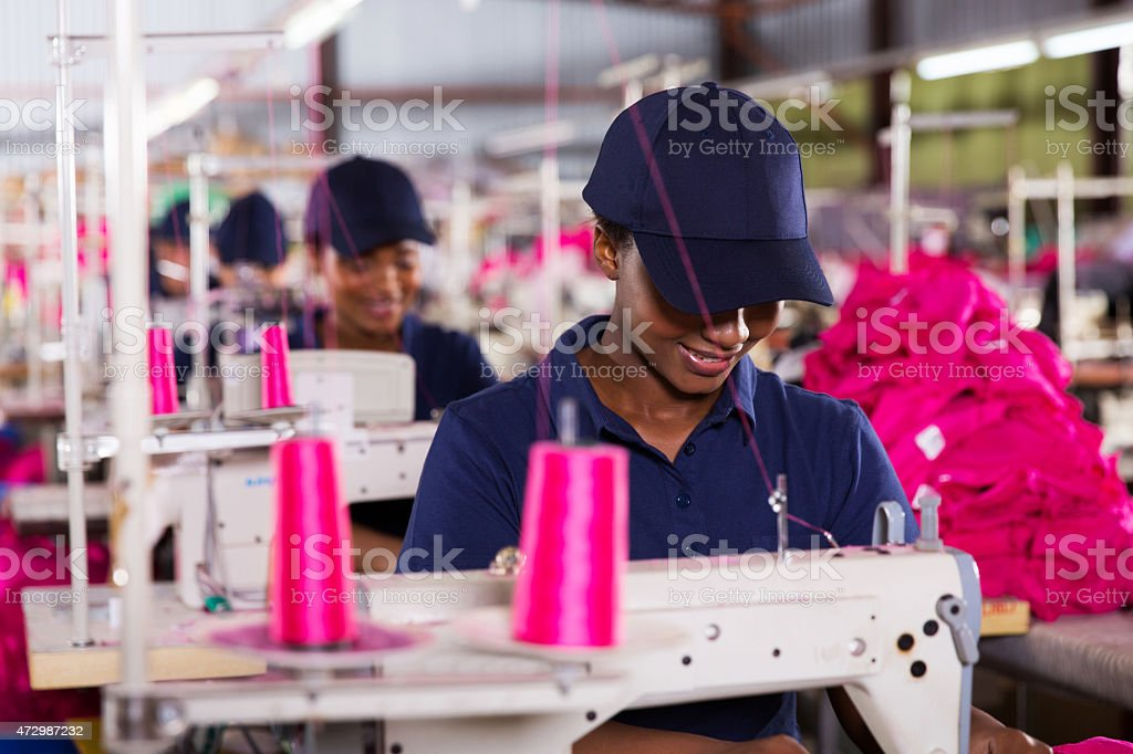 african worker sewing in clothing factory stock photo