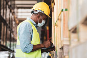 Black African worker wear protective face mask and helmet check stock in warehouse. Concept of new normal work in industry, factory after Covid 19 pandemic