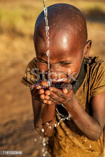 African young boy from Masai tribe drinking fresh water on savanna.  Potable water is very precious in Africa - women and children often walk long distances through the savanna to bring back jugs of water that they carry on their back. Maasai tribe inhabiting southern Kenya and northern Tanzania, and they are related to the Samburu.