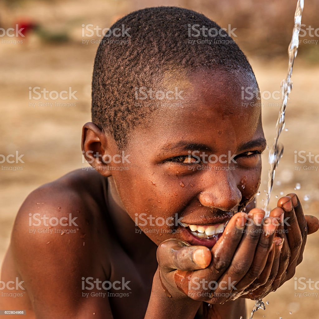African young boy drinking fresh water on savanna, East Africa​​​ foto