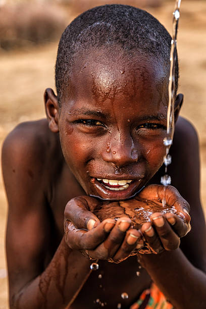 African young boy drinking fresh water on savanna, East Africa foto