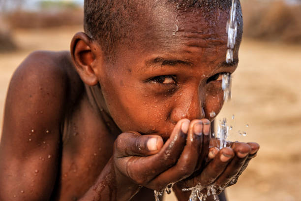 African young boy drinking fresh water on savanna, East Africa stock photo