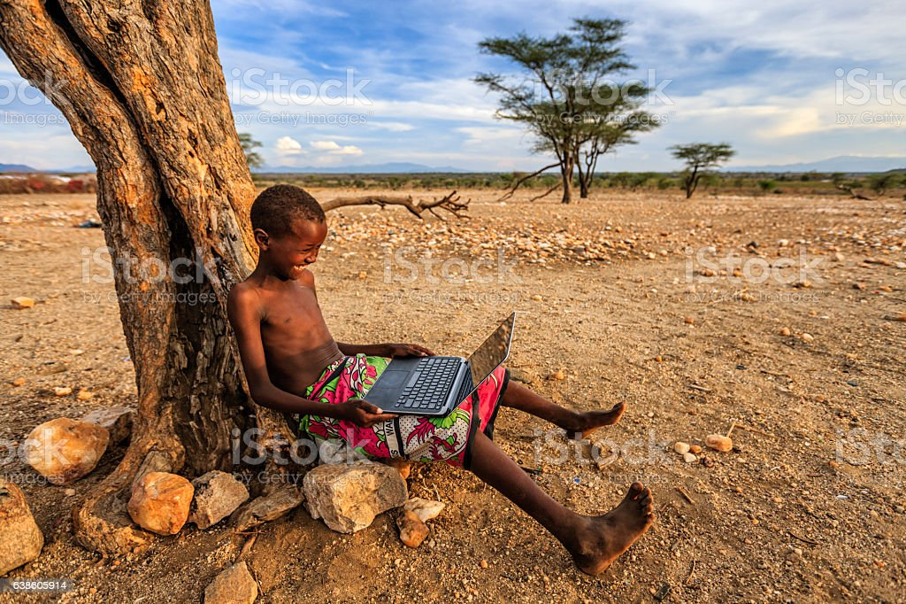 African young boy using laptop, Kenya, East Africa stock photo