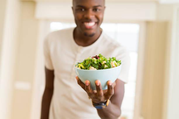 非洲年輕人拿著一碗健康沙拉微笑著歡快 - 沙律碗 個照片及圖片檔