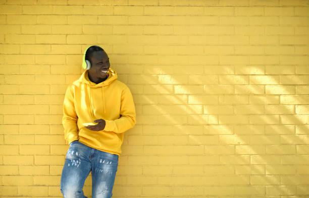 Afrikanischer junger Mann hört Musik leaning On Yellow Wall – Foto