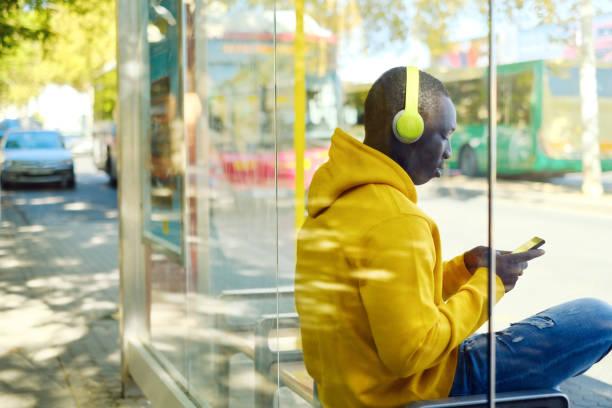 Afrikanischer junger Mann hört Musik an bushaltestelle – Foto